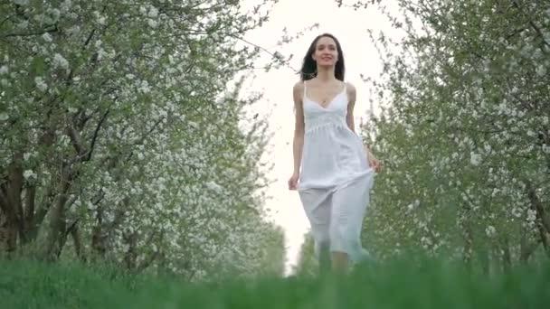 Jarní módní portrét krásné šťastné mladé ženy v bílých šatech s dlouhé hnědé vlasy běh a užijte si kvetoucí zahrada