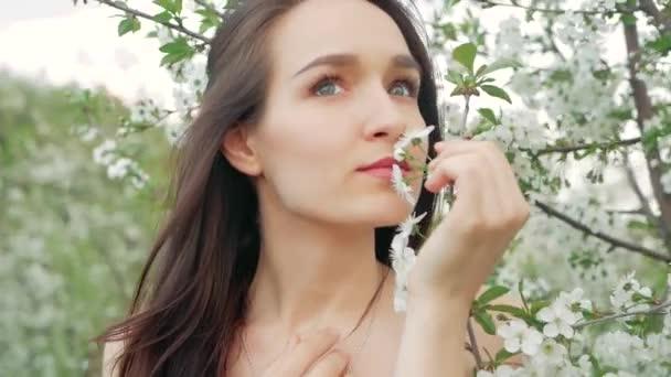 tavaszi divat portré egy szép boldog fiatal nő fehér ruhában, hosszú barna haja fut, és élvezze a szag a virágok virágzó kert