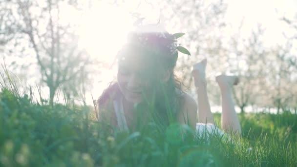 Szépség mosolygó lány feküdt a tavaszi rét a vadvirágok. Nevetett, és boldog. Élvezze a természetet. Gyönyörű fiatal nő szabadban.