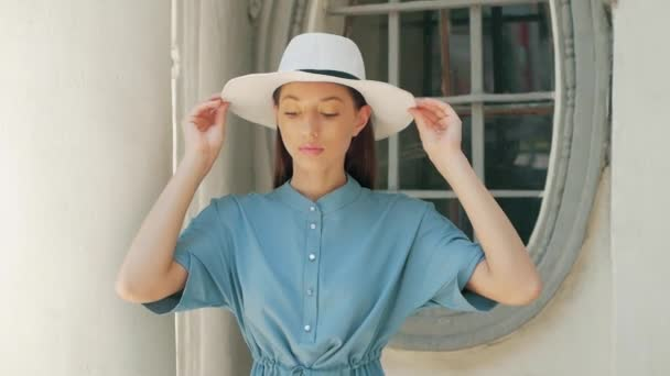 Portrait of Happy Stylish Charming young mixed race woman Fashion Blogger in blue summer dress and white hat posing on the summer street, sun is shining
