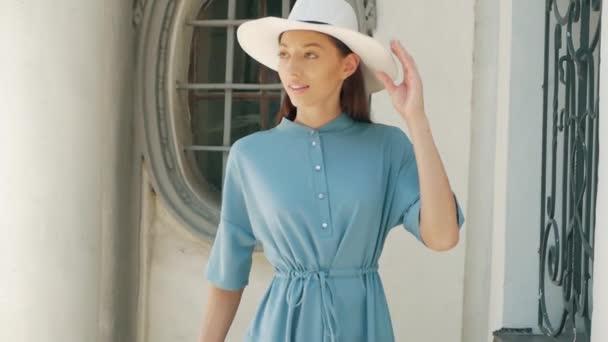 Porträt von Happy stilvolle charmante junge Mischlinge Frau Mode-Blogger in blauen sommerkleidchen und weißen Hut posiert auf der Sommer-Straße, ist die Sonne