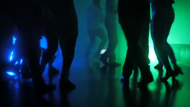 silhouette of legs of dancing people on latino salsa party with multi-colored iridescent lights