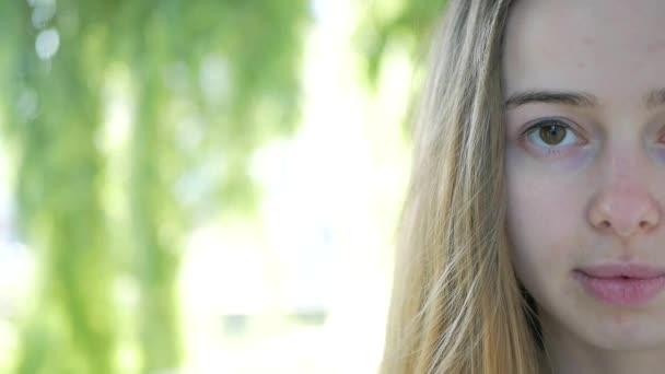 Detailní portrét krásné dívky při pohledu na fotoaparát. Polovinu její tvář