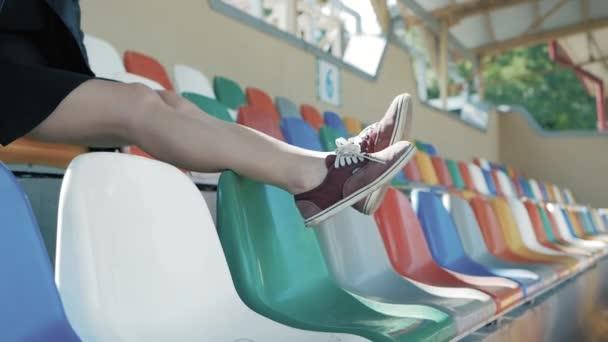 Die Beine einer Frau hängen auf Stühlen, im Fußballstadion. Füße in roten Turnschuhen
