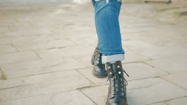 Closeup of young woman legs in black boots on cobblestone street