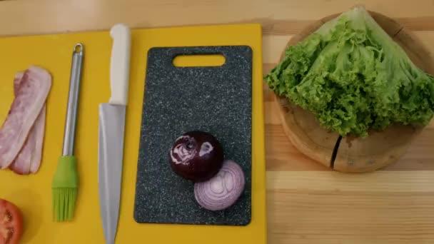 Kochen eines Sandwich in der Küche. Blick von oben auf das Set für ein Sandwich. Toastbrot, Speck, Soße, Zwiebeln, Tomaten, Salat auf Holztisch