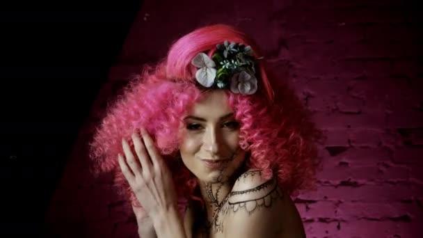 Portréja egy gyönyörű lány göndör rózsaszín hajú stílusos hajvágás. Szőtt a haj virágok. nevet, és flörtöl mosolyog a kamerába, a háttérben egy rózsaszín fal