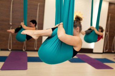 a group of women are hanging in a fetal position in a hammock. fly yoga class in the gym. Fit and wellness lifestyle