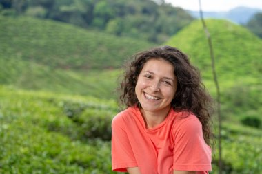 Beautiful brunette girl posing in the middle of the tea valley between green tea bushes