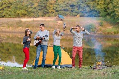 Gitarlı mutlu arkadaşlar, dışarıda eğleniyorlar, parkta göl kenarında dans edip zıplıyorlar güzel gökyüzü. Kamp eğlencesi.