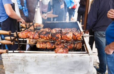 Barbecue skewers on open grill, people waiting tasty food.