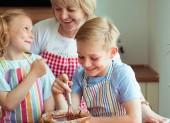 glückliche Großmutter mit ihren Enkeln beim Muffin- und Plätzchenbacken