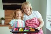 Porträt der glücklichen schönen Großmutter und ihrer Enkel in der modernen Küche, die Spaß beim Backen haben