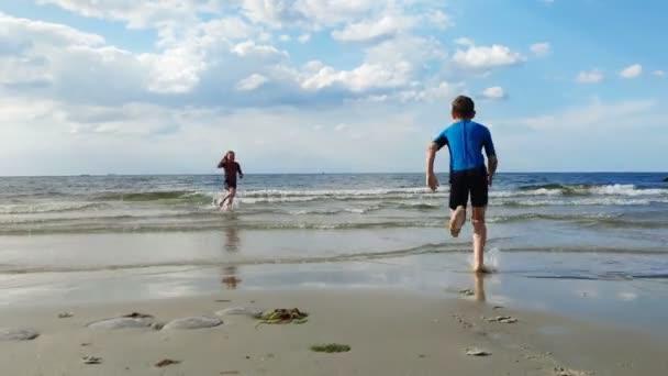 4K video dvou šťastných dětí v neoprenových plavkách běžících na pláži a hrajících si s vlnami v Baltském moři