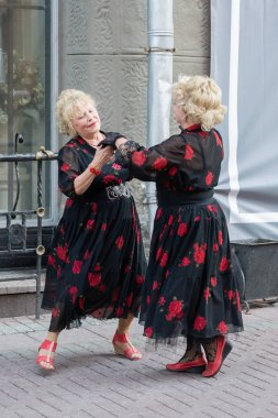 MOSCOW, RUSSIA - JUNE 3, 2018: Two women in same dresses dancing on street Old Arbat