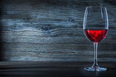 halfline wineglass with red wine on vintage wood