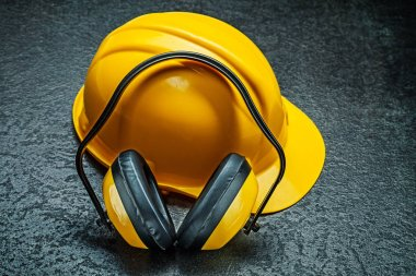 helmet with yellow earphones on black background