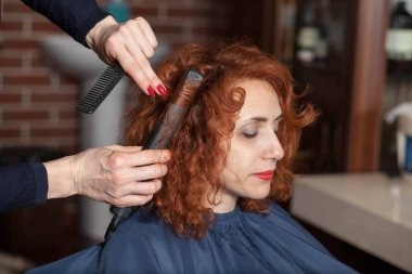 Redhead woman getting haircut by hairdresser in beauty salon