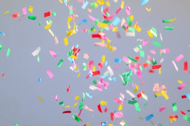 multicolored confetti on a grey background. Concept of holiday backdrop