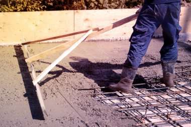 worker leveling fresh concrete slab with a special working tool