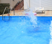 water splashes after the kids jump into the pool