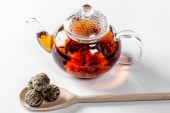 Tea in a glass teapot with a blooming large flower. Teapot with exotic green tea on a white background with dried balls-buds for tea brewing