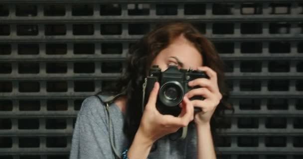 Teenager-Mädchen fotografiert mit Oldtimer-Filmkamera vor Metallzaun