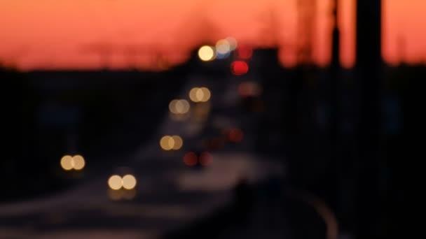 Highway provozu v noci rozostřené pozadí. Pohybující se kruhy bokeh noční dopravy. Auta se pohybují na silnici na mostě v večer. Dálnice ve tmě.