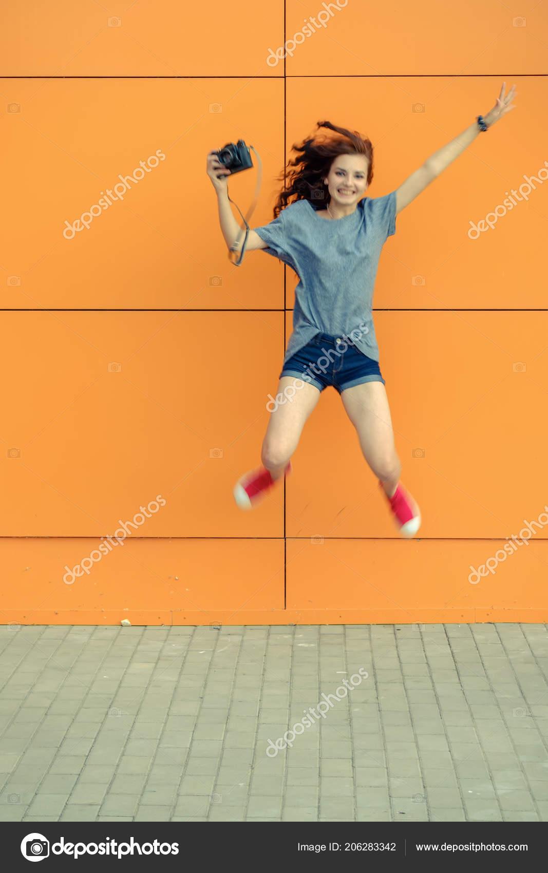 1aab72cca18dbd Mooi meisje jamping met vintage camera voor oranje muur — Stockfoto ...