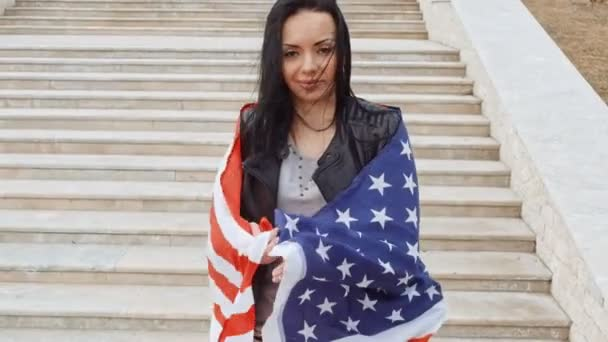 Brunette woman warapped in US flag posing in front of stairs leading up