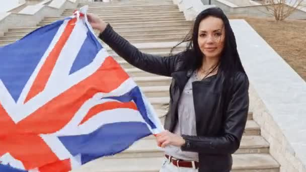 Černé vlasy žena držící v rukou Union Jack vlajka mávala na vítr