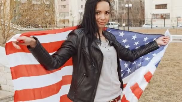 Latino girl with wavin United States flag in hands behind her back looking  at camera and smiling