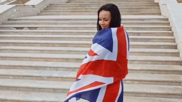Šťastná žena, zabalené v britskou vlajkou před schody vedoucí nahoru