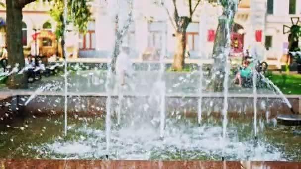 Parkbrunnen in Zeitlupe mit unkenntlich gemachten Senioren im Hintergrund