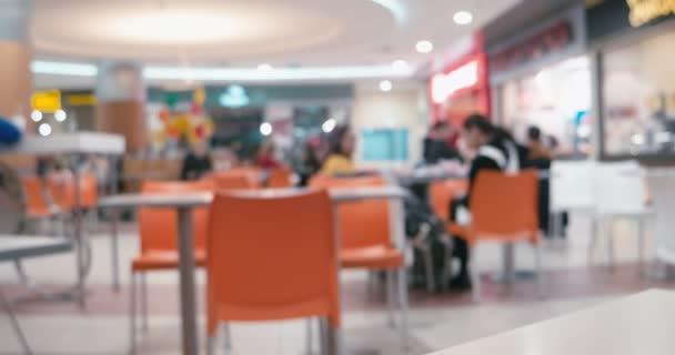 K nepoznání lidí jíst fast food timelapse v obchoďáku jídlo soudu sedí na židlích, oranžová barva