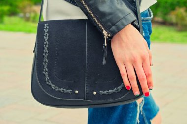 Young woman hold yoyr hand over the black handbag on her shoulder wearing riped jeans