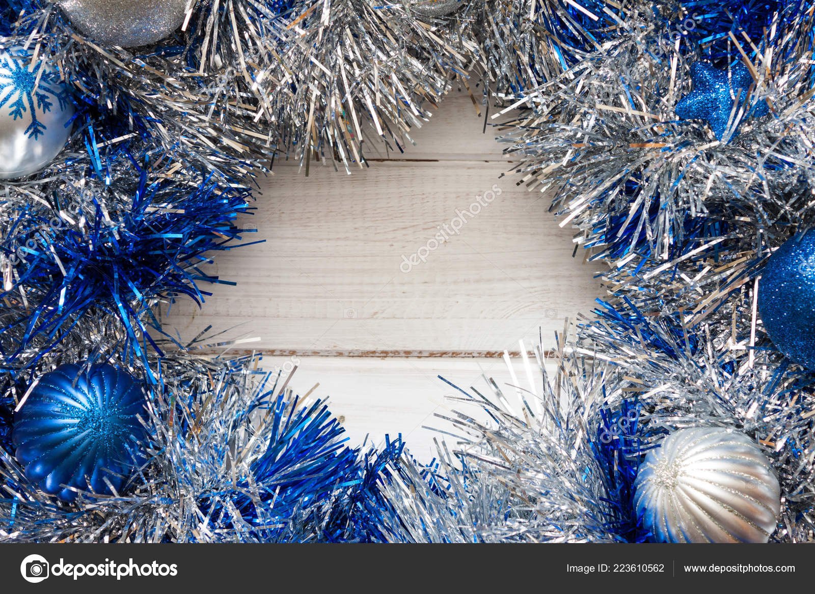 Blue and silver Christmas wreath with decorations on white wooden background.– stock image
