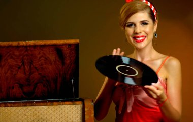 Retro woman with music vinyl record. Girl pin-up style wearing red dress.