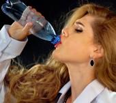 Fotografia Idratazione in ufficio. Denti sensibili donna bottiglia fredda acqua potabile