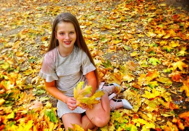 Autumn fashion dress child girl sitting fall leaves park outdoor.