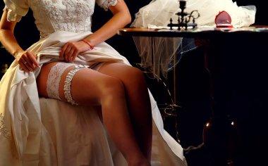 Wedding night preparing garter. Bride undressing.