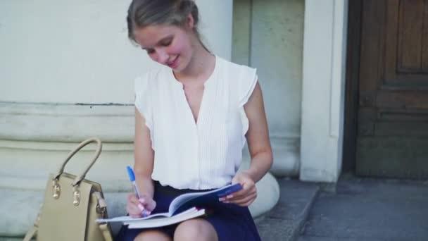 Higher education happy girl freshwoman student sitting on university steps