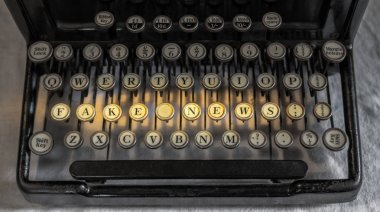 Fake News spelled out on old vintage portable typewriter  with financial accounting key in UK pounds sterling stock vector