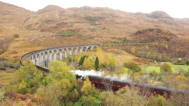 Steam train crossing Glenfinnan viaduct in Scotland. Famous train journey in Scottish Highlands with beautiful landscape and scenery. Transportation and travel concepts