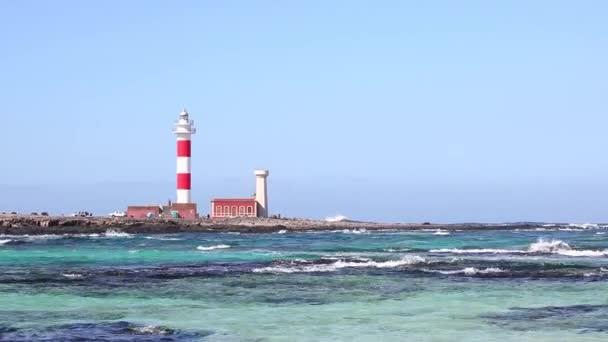 Meerblick auf Fuerteventura mit klarem Wasser und Leuchtturm im Hintergrund. gibt es einige schwarze Felsen auf Vorder- und Unterwasser. Sommer- und Reisekonzepte.