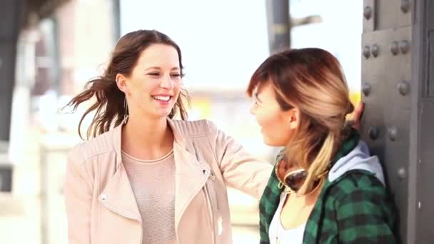 Gruppo di amici divertendosi ad Amburgo. Sono due donne, un giapponese e un tedesco e un uomo mediorientale, che ridono e che abbracciano. Concetti di amicizia e di stile di vita.