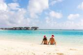 Pár s vánoční Santa hat relaxaci u moře. Dovolená tropický cíl pohlednice pro sezónu dovolenou s vánočními klobouky. Muž a žena seděla na písku a koukal, cestování a dovolená pojmy