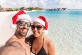 Fotografie Usmívající se pár s vánoční Santa hat pořizování selfie v přímořské. Dovolená tropický cíl pohlednice pro sezónu dovolenou s vánočními klobouky. Šťastný muž a žena při pohledu na fotoaparát.