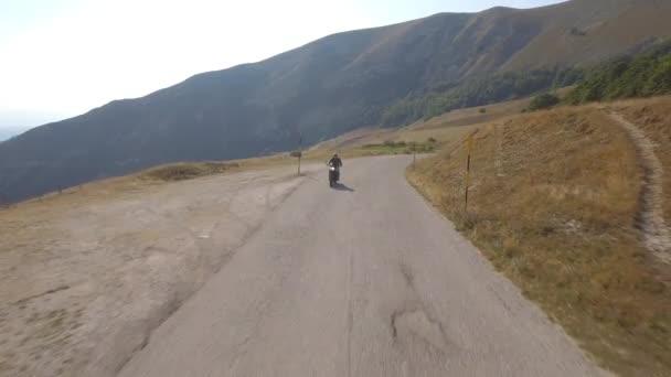 Letecký pohled na člověka, jízdy na motorce na horské silnici. Hukot video z motocyklu na cestě, vinoucí krajinou. Koncepce dopravy a cestování