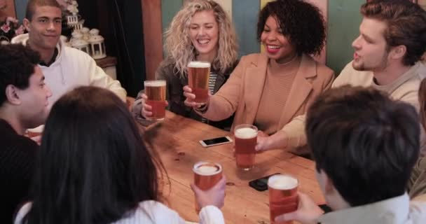 Group of friends enjoying a beer at pub in London, toasting and laughing